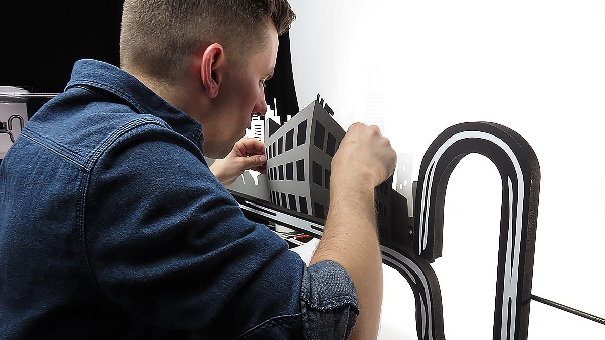 An artist from Ink Factory adjusts a building for Perimeter Architect's stop motion video