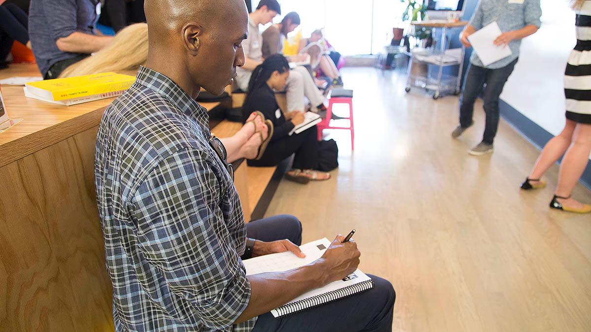 A co-op member draws in his sketchbook during the workshop