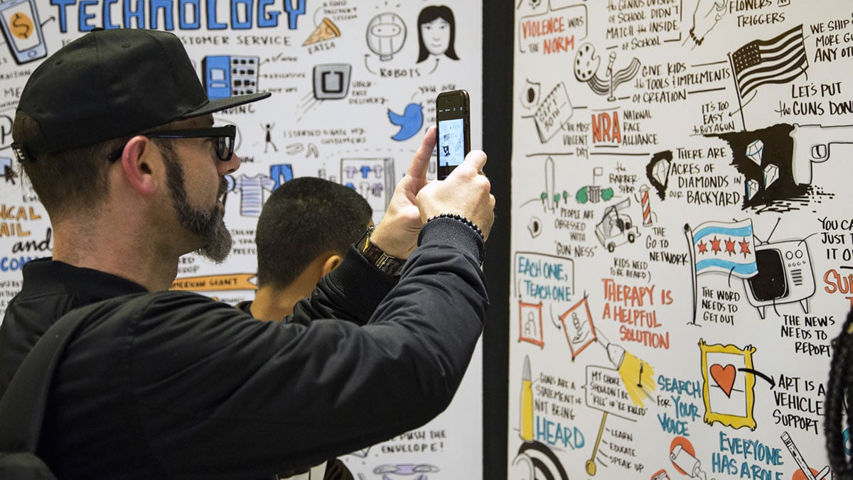 A Chicago Ideas attendee takes a photo of the visual notes Ink Factory created live