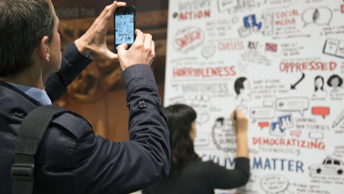 An attendee snaps a photo of an artist drawing live at Chicago Ideas Week
