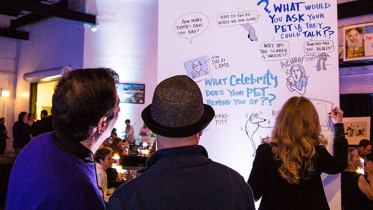 Attendees watch Ink Factory artists create visual notes for the Puppy mill Project