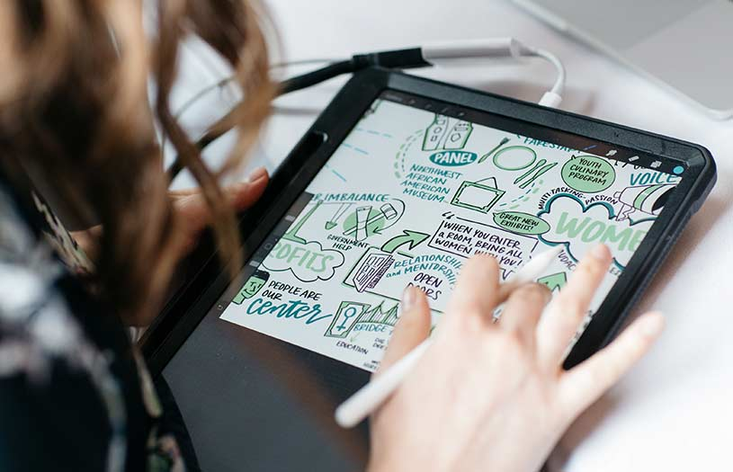 An Ink Factory artist creates visual notes on an iPad Pro with an apple pencil.