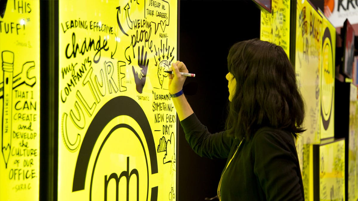 An artist from Ink Factory draws visuals on Maestro Health's trade show booth at a conference