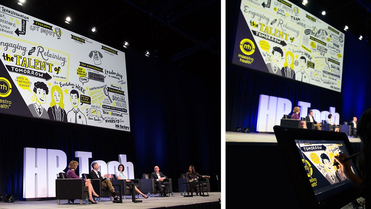 A panel discussion live on stage while an artist creates digital visual notes on screen