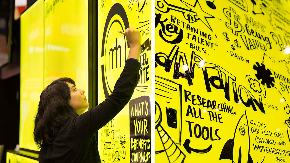 An artist draws visual notes on an LED light up trade show booth