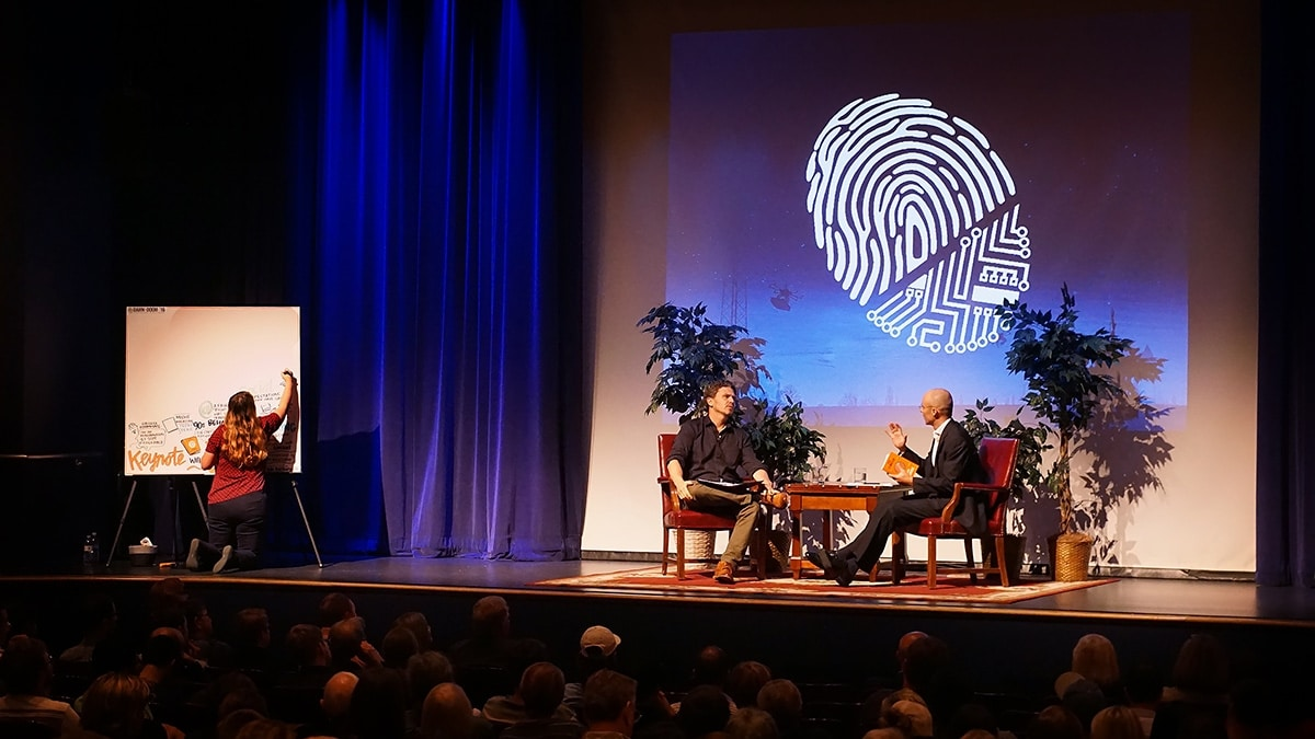 An artist from Ink Factory draws live on stage during a talk at Dawn or Doom