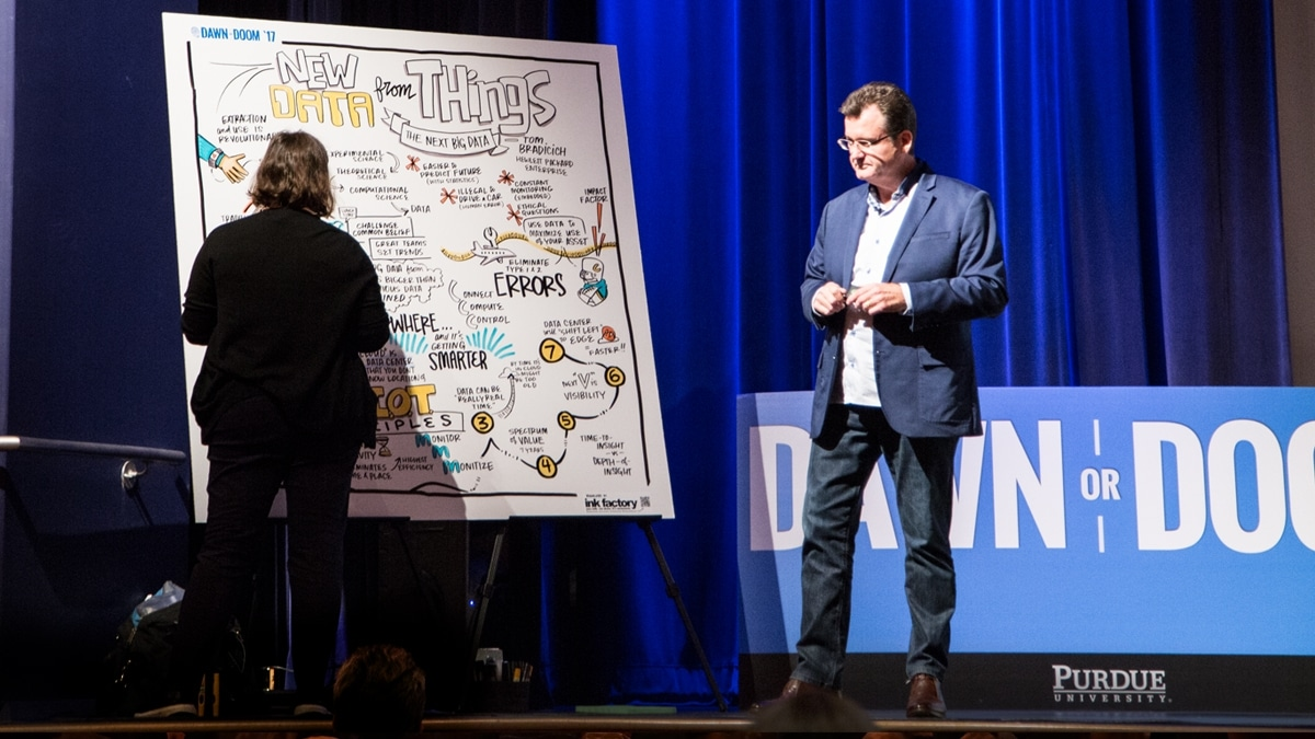A visual note-taker draws on stage next to a speaker at Dawn or Doom