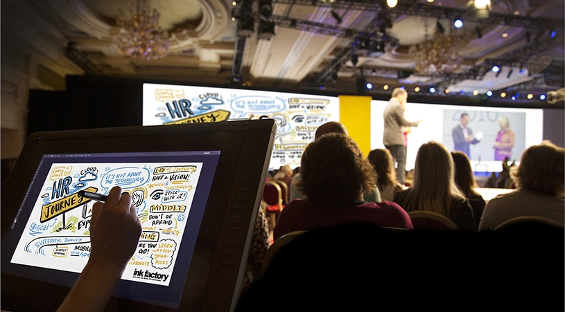 A visual note-taker draws at a conference digitally