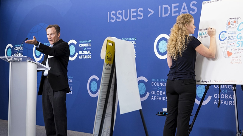 An artist draws visual notes live on stage at the Chicago Council on Global Affairs Keynote