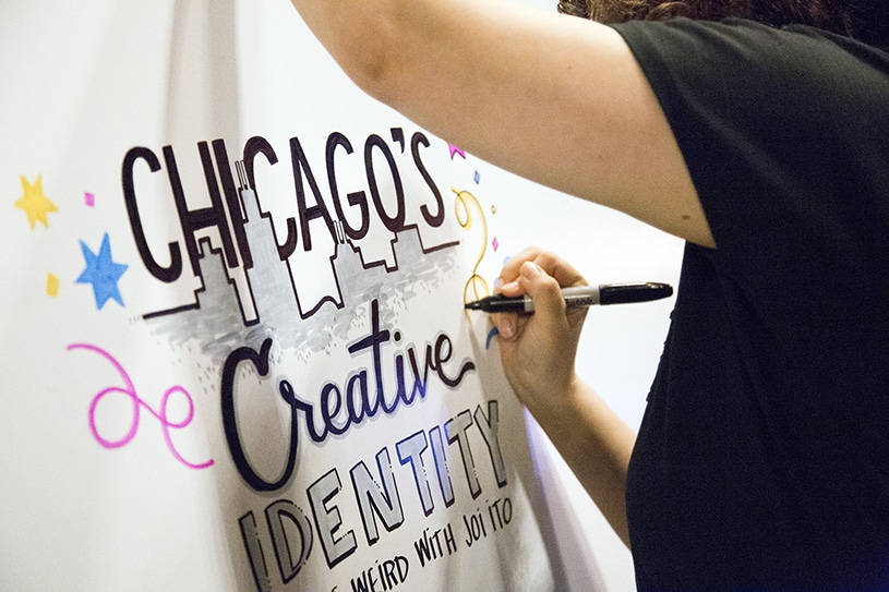 An artist draws a title of a graphic recording on a board