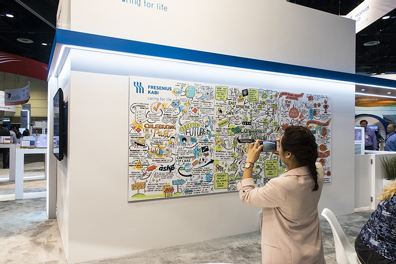 An attendee snaps a photo of Ink Factory's visual notes at the Fresenius Kabi conference booth