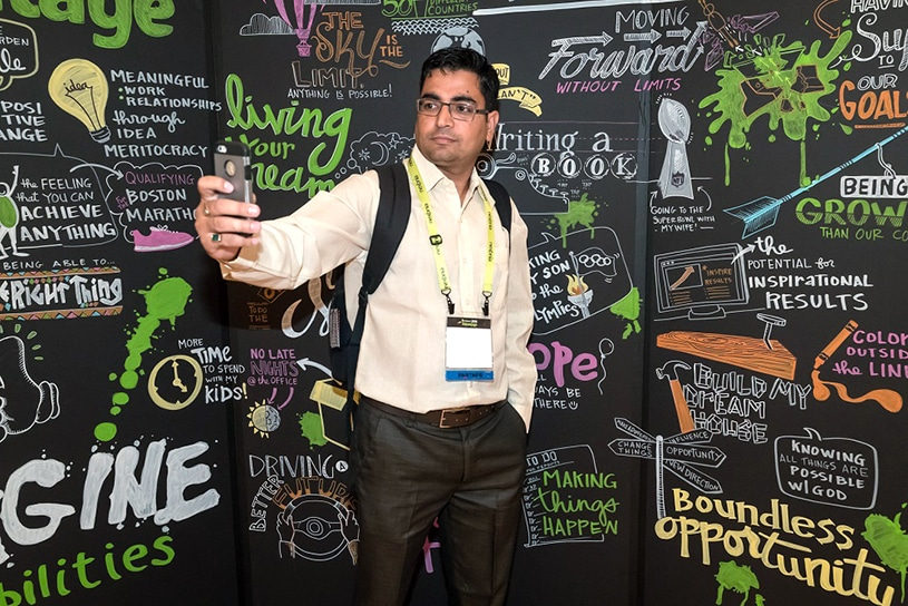 A conference attendee takes a selfie against a wall of visual notes