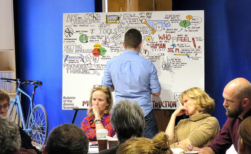 An artist creates visual notes live during an internal meeting for the Bulletin of Atomic Scientists