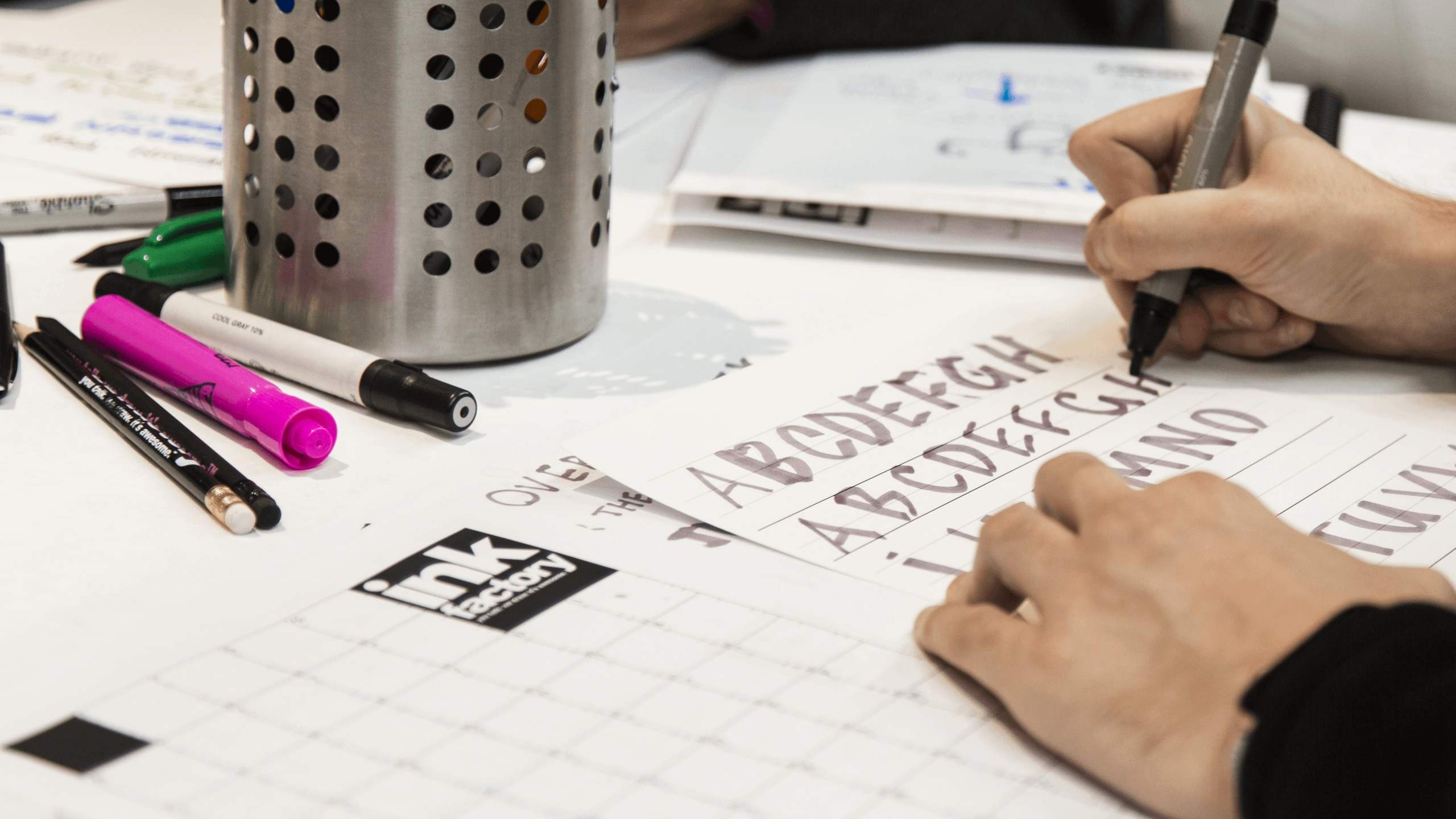 Someone practices drawing their handwriting during an Ink Factory workshop