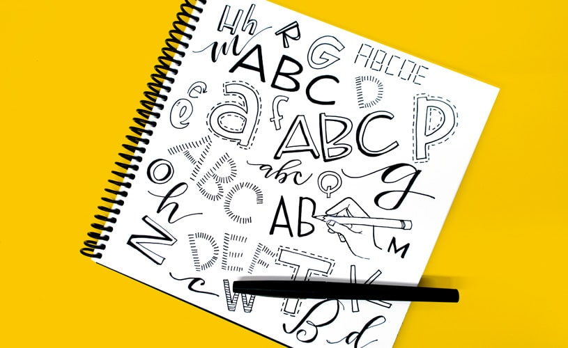 Various letters drawn in a sketchbook