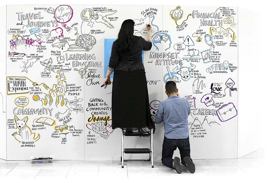 Two artists create live visual notes on a large mural