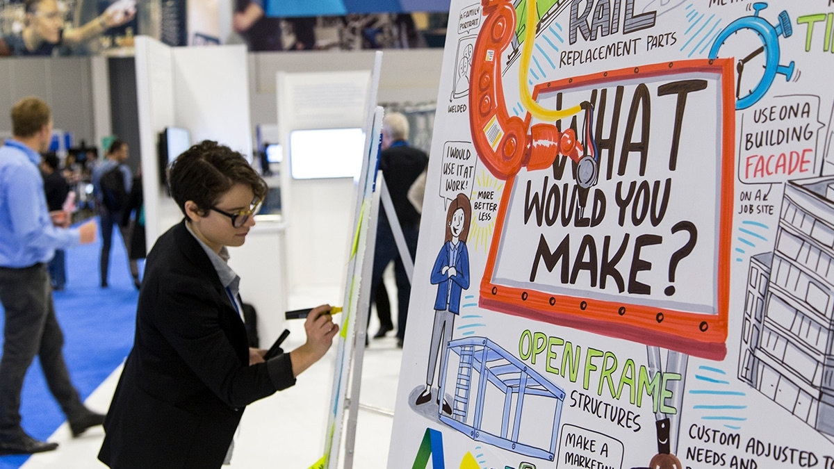 An Ink Factory artist draws attendee responses live at the Make AU booth