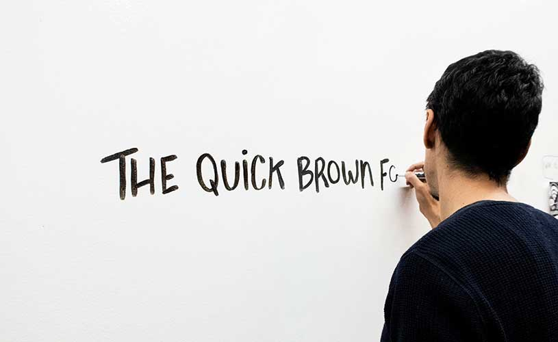 Artist practices handwriting on whiteboard