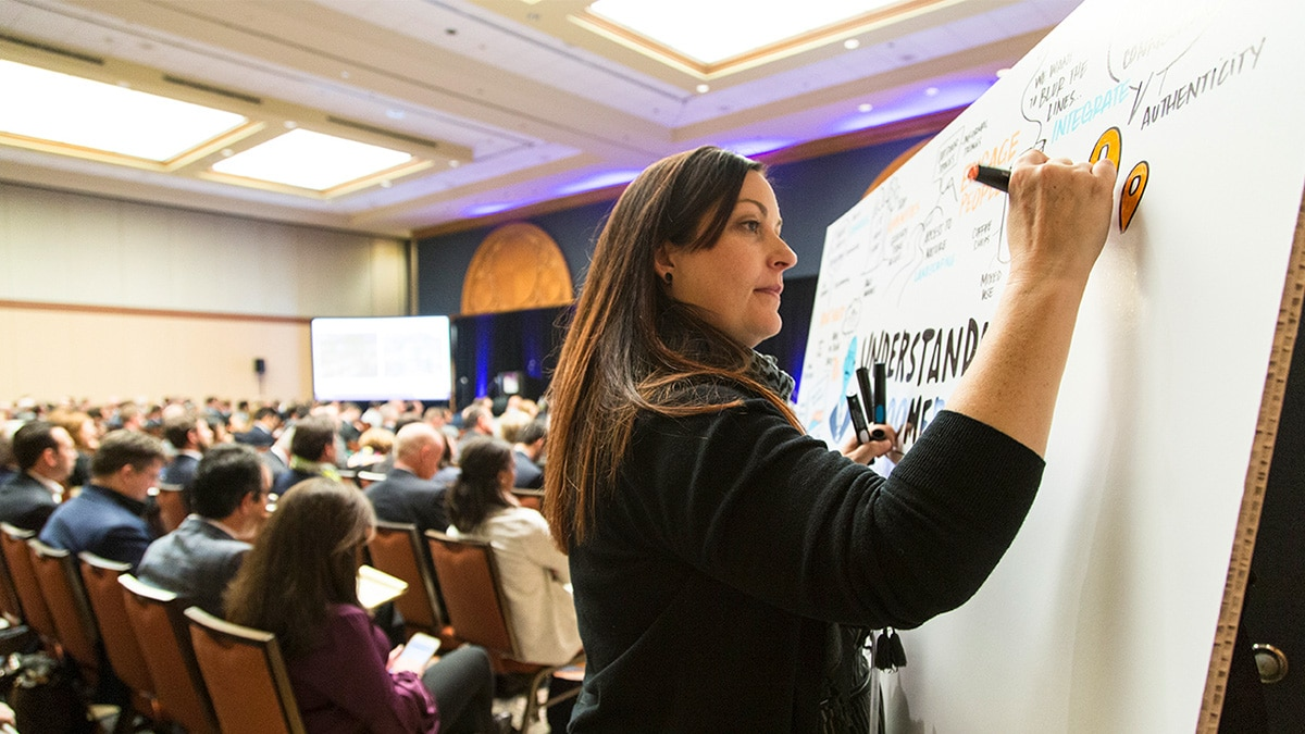 A visual note-taker draws live in a large meeting