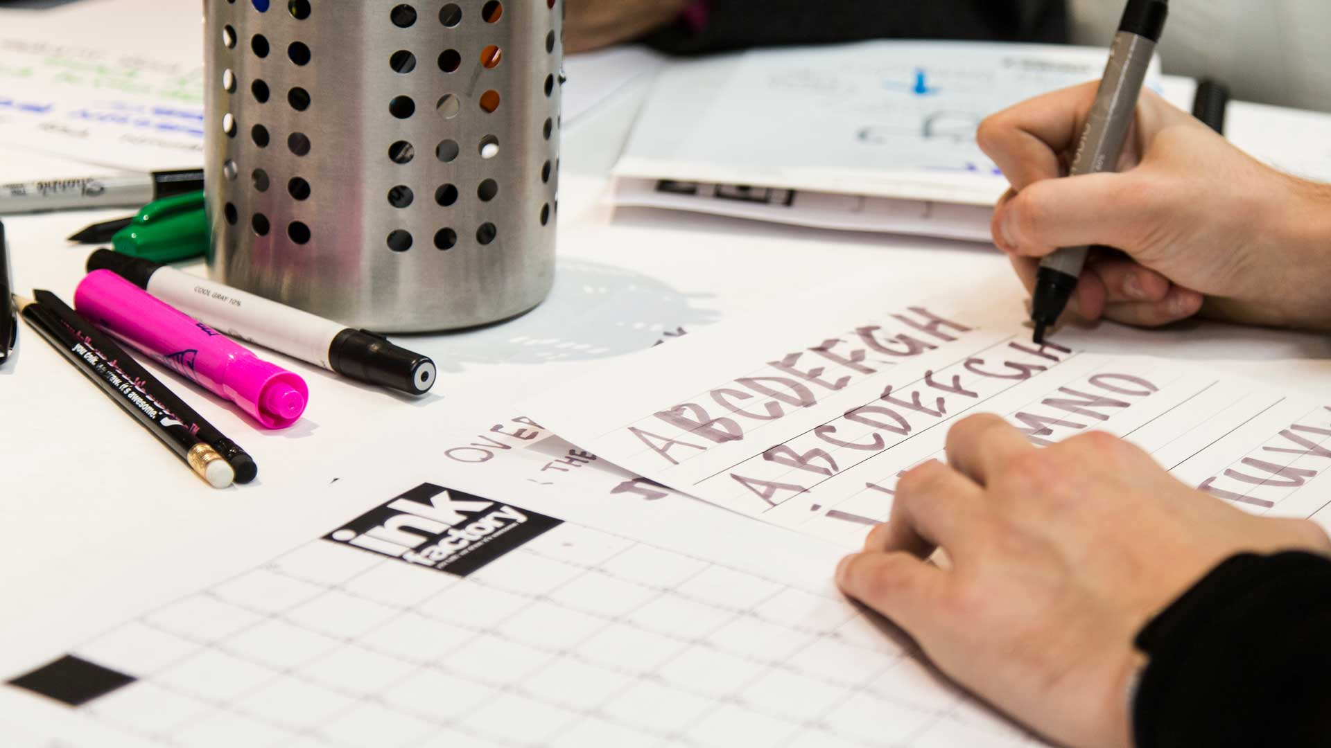 A student practices hand lettering in a visual note workshop