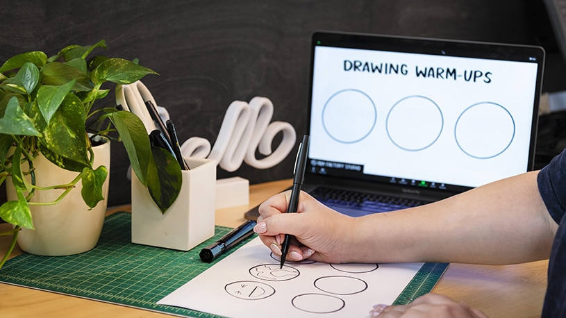 An artist draws icons during a virtual visual notes workshop